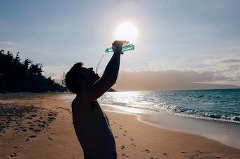 Touriste qui boit de l'eau sur une plage de Guadelouep