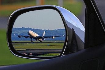 Reflet d'un avion à travers le miroir d'un rétro-viseur d'une voiture de location